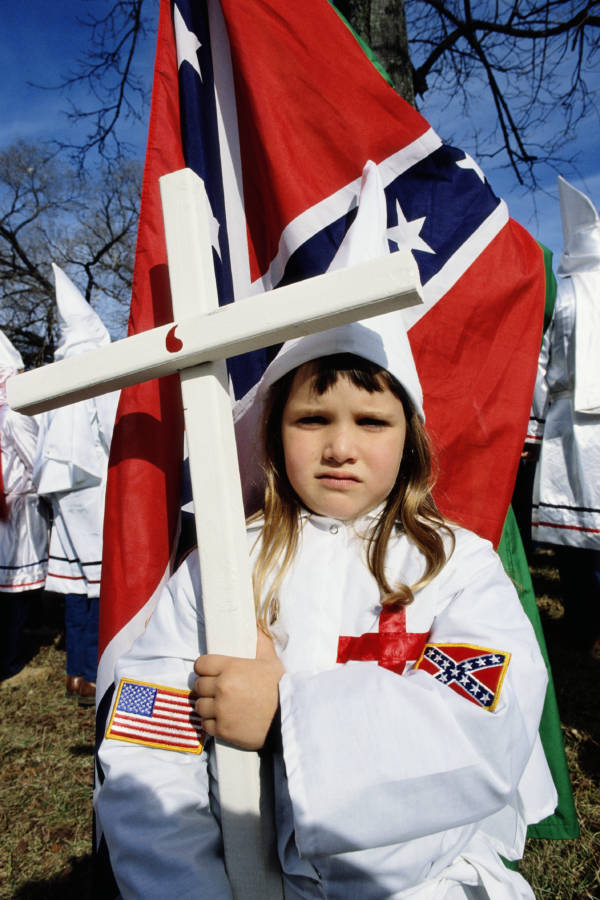 A Ku Klux Klan Kid Posing With A Cross