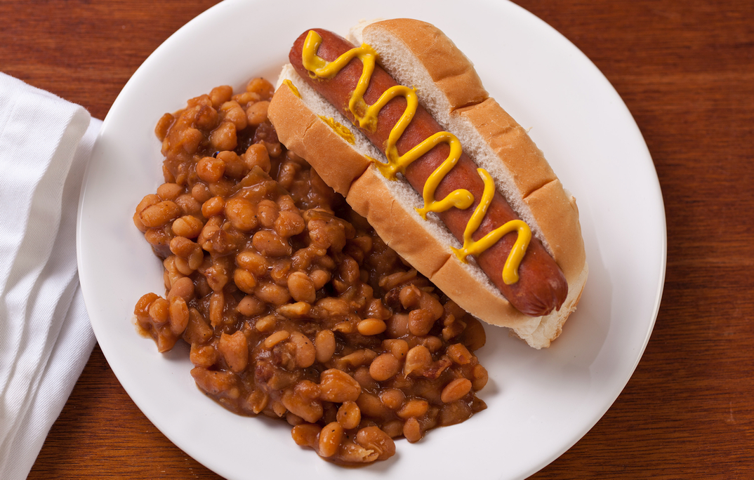 a hot dog with mustard and baked beans