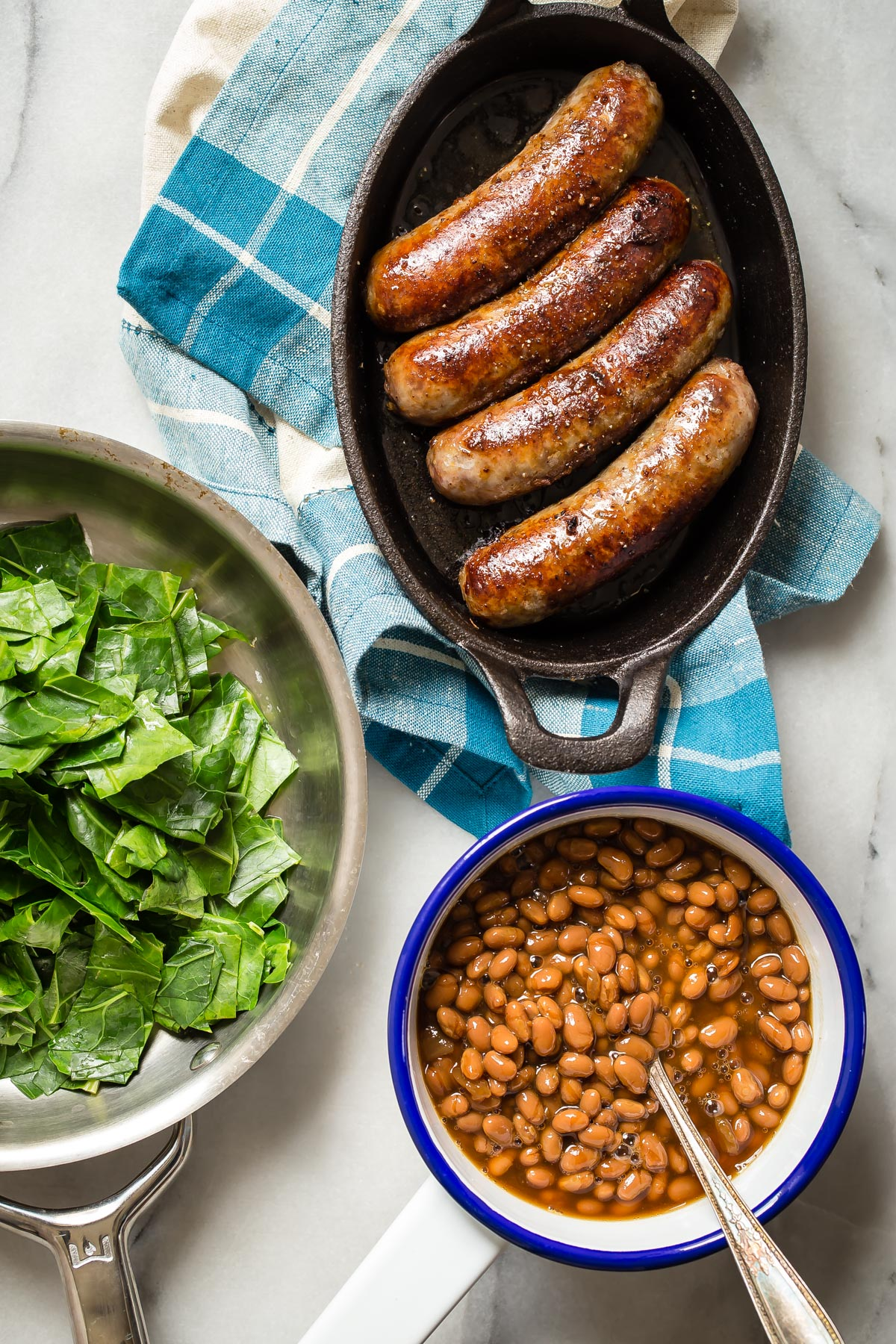 bratwurst sausages with baked beans and collard greens
